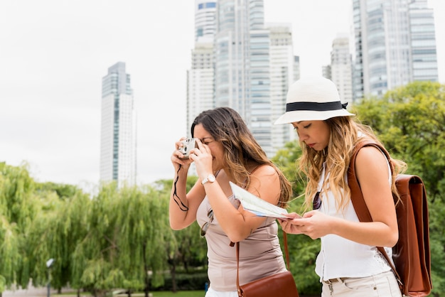 Young woman wearing hat reading the map and her female friend taking photograph from camera Free Photo