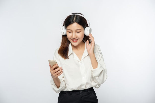 Young woman wearing headphones and listening to music on a smartphone Free Photo