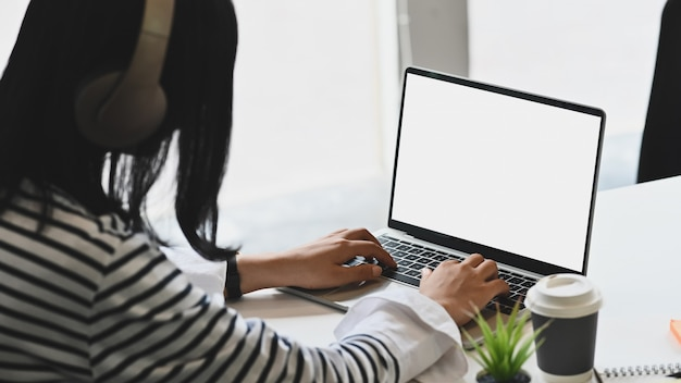 Young woman wearing headphones and using isolated white screen of laptop computer. Premium Photo