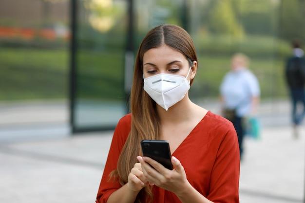 Young woman wearing kn95 ffp2 mask using mobile phone app in city street to aid contact tracing and self diagnostic in response to coronavirus Premium Photo