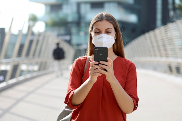 Young woman wearing kn95 ffp2 mask using smart phone app in modern city street Premium Photo
