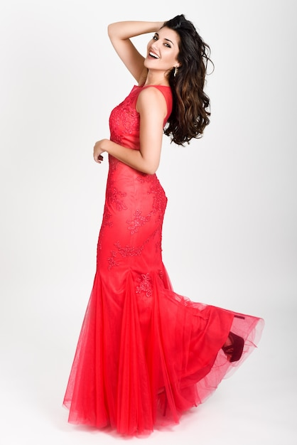 Young woman wearing long red dress on white background ...