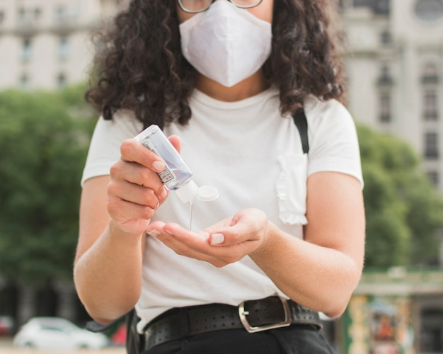Young woman wearing a medical mask using hand sanitizer Free Photo