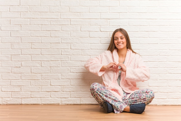 Young woman wearing pajama doing a heart shape with hands Premium Photo