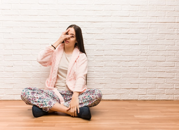 パジャマを着ている若い女性は恥ずかしさと同時に笑って Premium写真