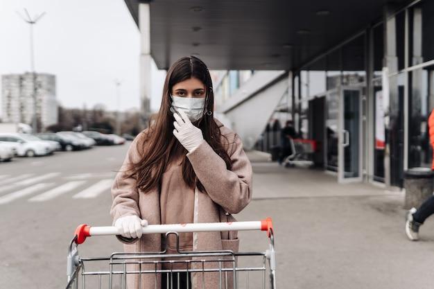 Young woman wearing protection face mask against coronavirus 2019-ncov pushing a shopping cart. concept of coronavirus Free Photo