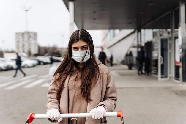 Giovane donna che indossa una maschera protettiva contro il coronavirus 2019-ncov che spinge un carrello. Foto Gratuite