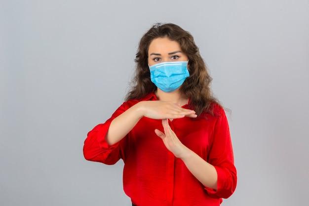 Молодая женщина в красной блузке в медицинской защитной маске выглядит уставшей и скучающей, делая жест тайм-аута руками на изолированном белом фоне Бесплатные Фотографии