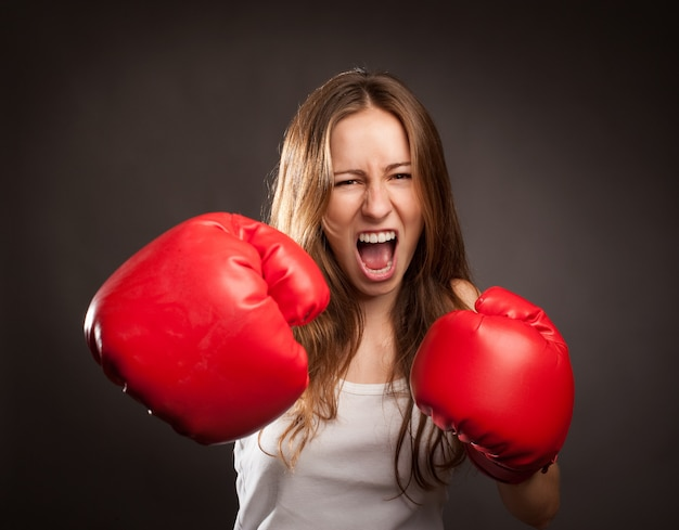 Young woman wearing red boxing gloves Premium Photo