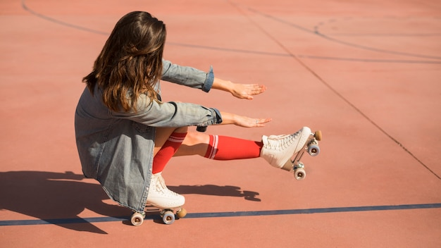 Young woman wearing roller skates crouching and stretching her legs and hand on court Free Photo