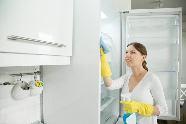 Young woman wearing rubber gloves cleaning the fridge Free Photo