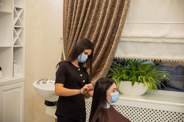 安全マスクを身に着けている若い女性は、保護医療マスクで美容師によって散髪を取得します Premium写真