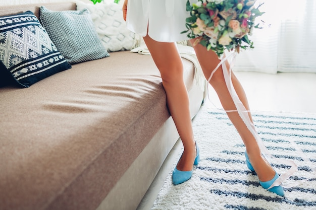 Young woman wearing silk dressing gown and blue shoes and holding bouquet at home, bride on wedding day Premium Photo