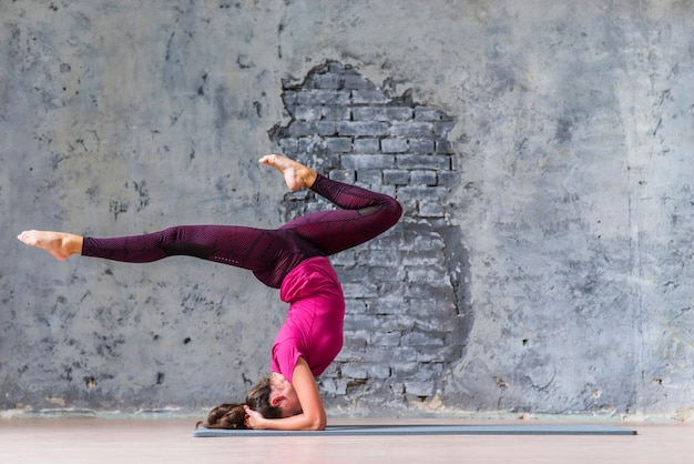Young woman wearing sportswear working out against grey wall Free Photo
