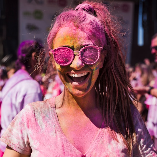 Young woman wearing sunglasses covered with holi color Free Photo