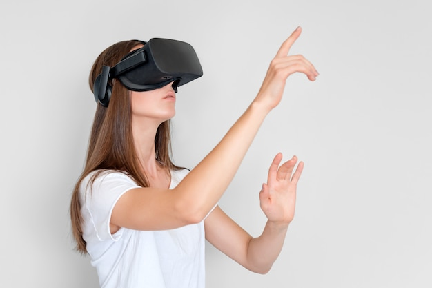 Young woman wearing virtual reality goggles headset, vr box. connection, technology, new generation, progress concept. girl trying to touch objects in virtual reality. studio shot on gray Premium Photo
