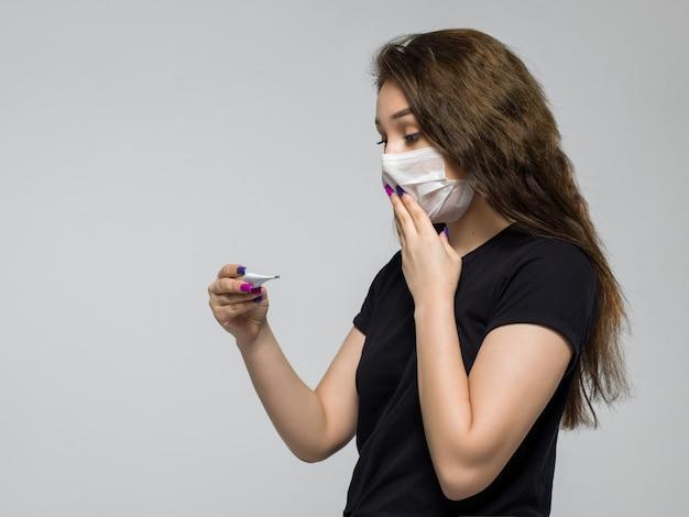 La giovane donna che indossa la maschera medica bianca è sorpresa dopo aver esaminato un termometro Foto Gratuite