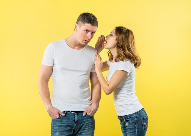 Young woman whispering on boyfriend's ear against yellow background Free Photo