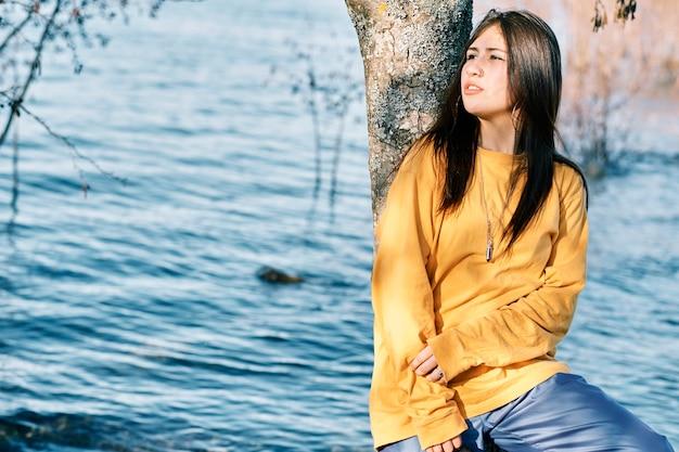 Молодая женщина в стиле хип-хоп отдыхает на природе рядом с озером. Premium Фотографии