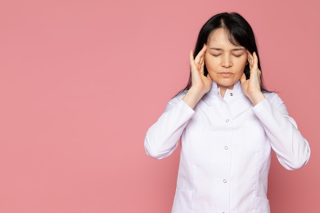 Young woman in white medical suit having a severe headache on pink Free Photo