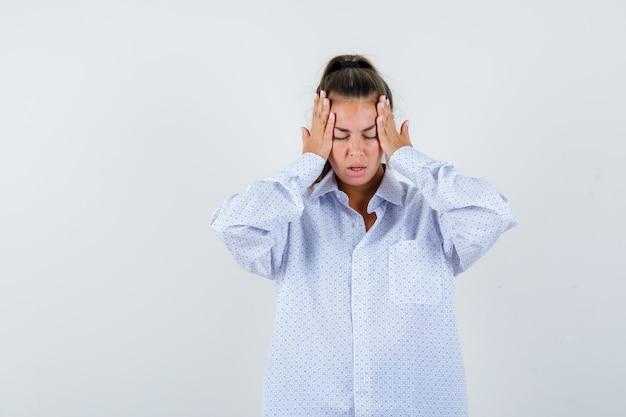Giovane donna in camicia bianca che tiene le mani sulle tempie e sembra stanca Foto Gratuite