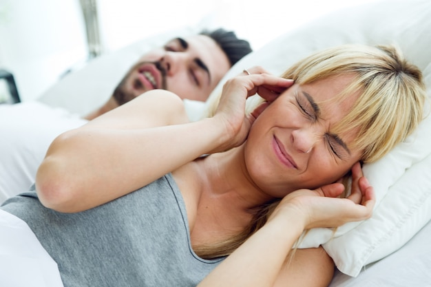 Young woman who can not sleep because her husband snores. Free Photo