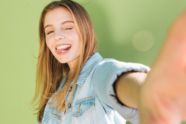 Young woman winking and sticking out her tongue taking selfie against green background Free Photo