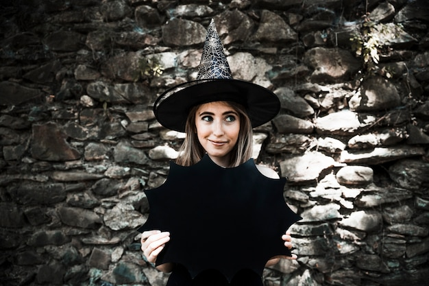 Young woman in witch hat holding halloween decoration and looking away Free Photo