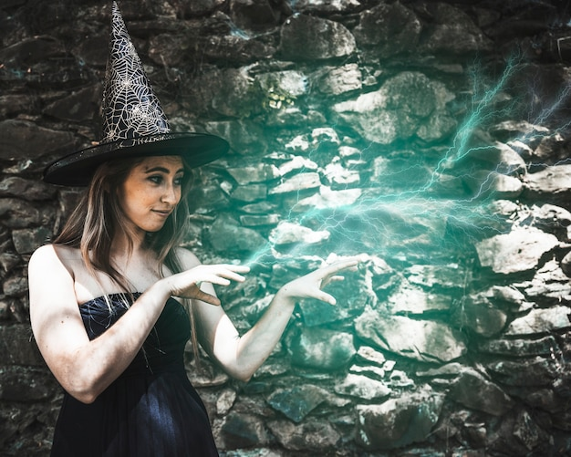 Young woman in witch hat pretending magic Free Photo