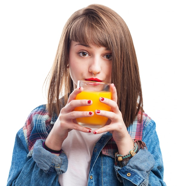 Young woman with a glass of orange juice close to her lips Free Photo