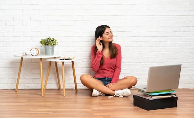 屋内の床に座って、耳に手を置いて何かを聞いているラップトップを持つ若い女性 Premium写真