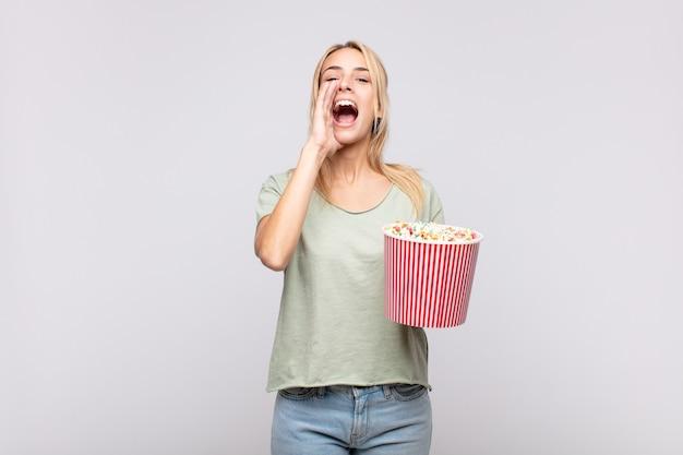 Молодая женщина с ведром попкорна чувствует себя счастливой, взволнованной и позитивной Premium Фотографии