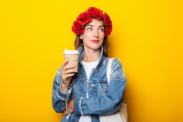 笑顔の若い女性がデニムジャケットを着て横を向いており、頭に赤い花の花輪が黄色い壁にコーヒーと紙コップを持っています。 Premium写真