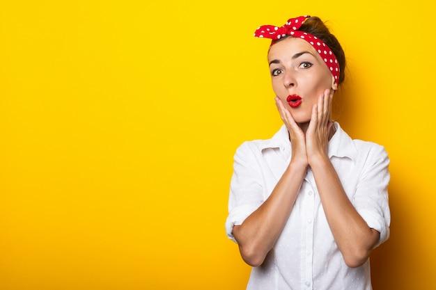 Молодая женщина с удивленным лицом держит руки на подбородке, в очках и повязке на голове на желтой стене. баннер. Premium Фотографии