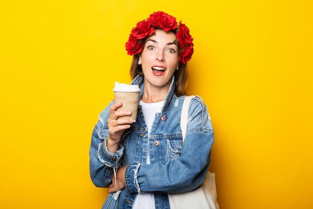 デニムジャケットに驚いた顔と黄色の壁にコーヒーと紙コップを保持している彼女の頭に赤い花の花輪を持つ若い女性。 Premium写真