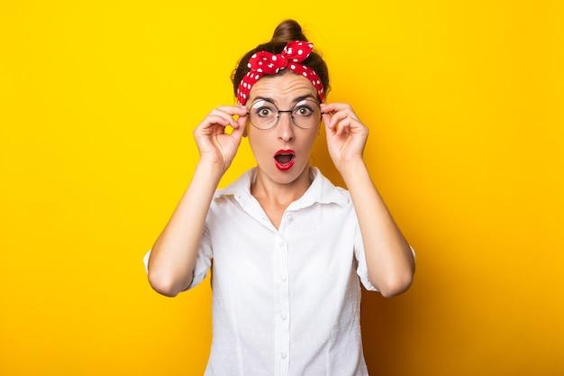 黄色い壁の彼女の頭に眼鏡とヘッドバンドを身に着けている驚きの顔を持つ若い女性。 Premium写真