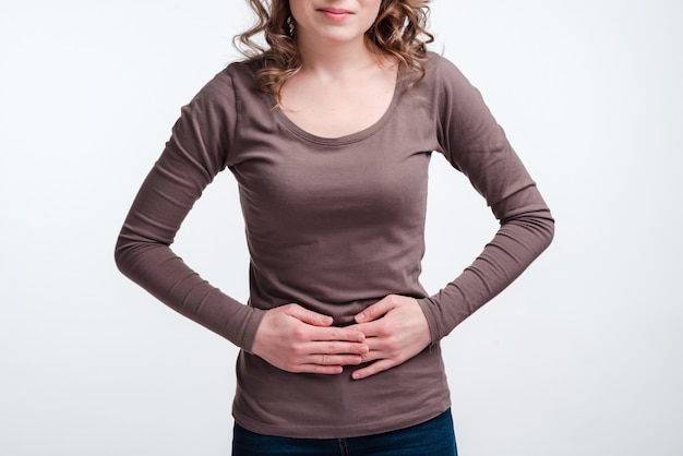 Young woman with abdominal pain close up, stomach pain clutching her stomach Premium Photo