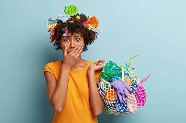 플라스틱 폐기물 가방을 들고 아프로 머리와 젊은 여자 무료 사진