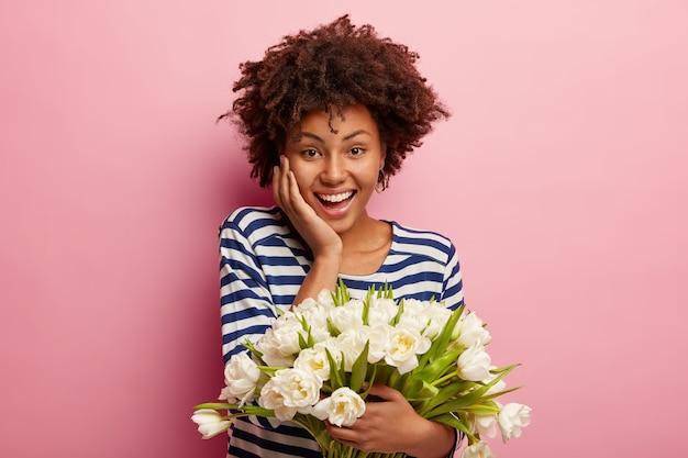 흰 꽃의 꽃다발을 들고 아프로 머리를 가진 젊은 여자 무료 사진