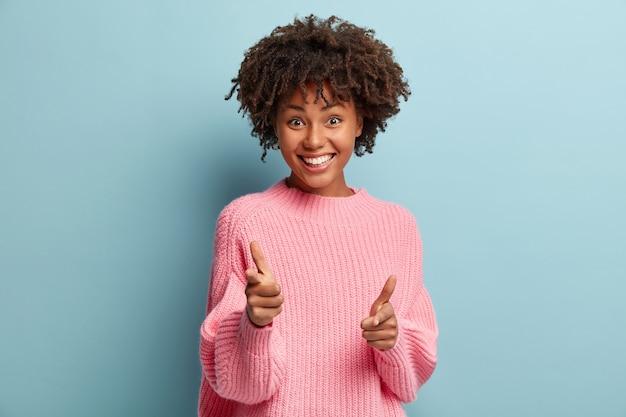 Giovane donna con taglio di capelli afro che indossa un maglione rosa Foto Gratuite
