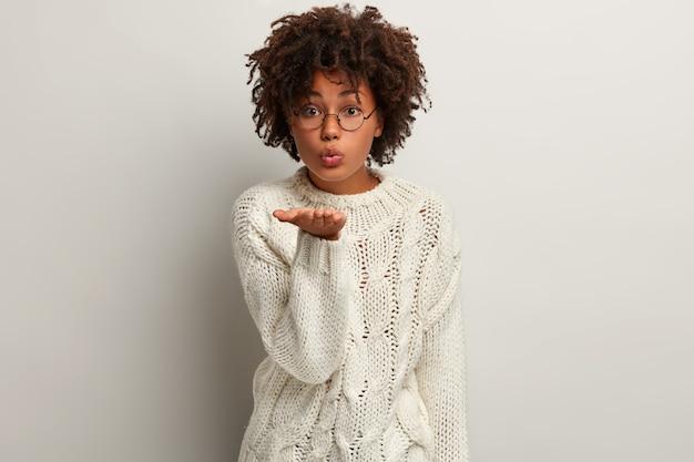 흰색 스웨터를 입고 아프로 머리를 가진 젊은 여자 무료 사진