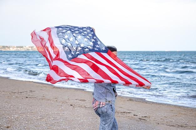 Una giovane donna con una bandiera americana corre in riva al mare. il concetto di patriottismo e celebrazioni del giorno dell'indipendenza. Foto Gratuite