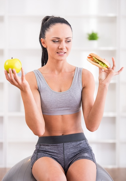 Young woman with apple and hot dog after exercising at home. Premium Photo