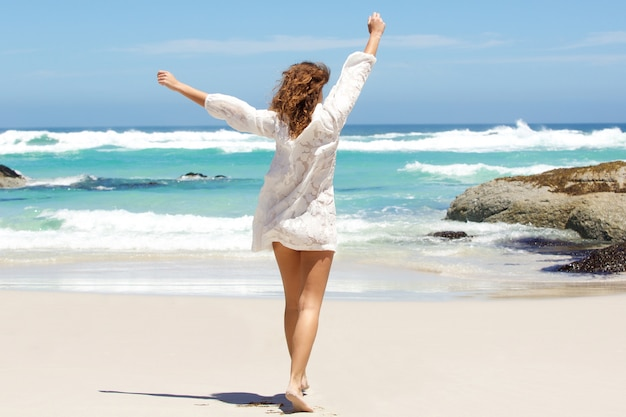 Young woman with arms raised in the air at the beach Premium Photo