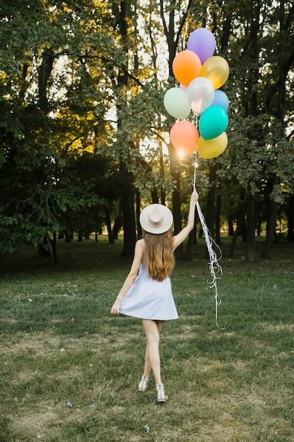 屋外の風船を持つ若い女性 無料写真