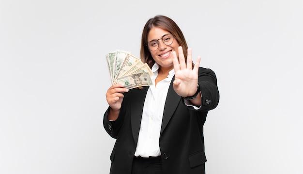 Молодая женщина с банкнотами улыбается и выглядит дружелюбно, показывает номер четыре или четвертый с рукой вперед, отсчитывая Premium Фотографии