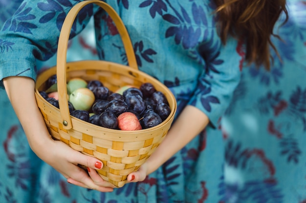 Young woman with a basket of fruits, plums and apples. Free Photo