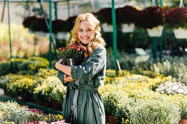 美しいブロンドの髪と優しい笑顔の若い女性は、ベルト付きの緑のローブを着て温室で働いています 無料写真