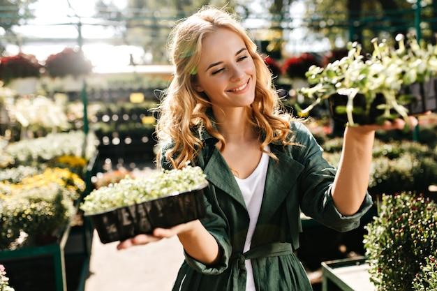 Молодая женщина с красивыми светлыми волосами и нежной улыбкой, одетая в зеленый халат с поясом, работает в теплице Бесплатные Фотографии
