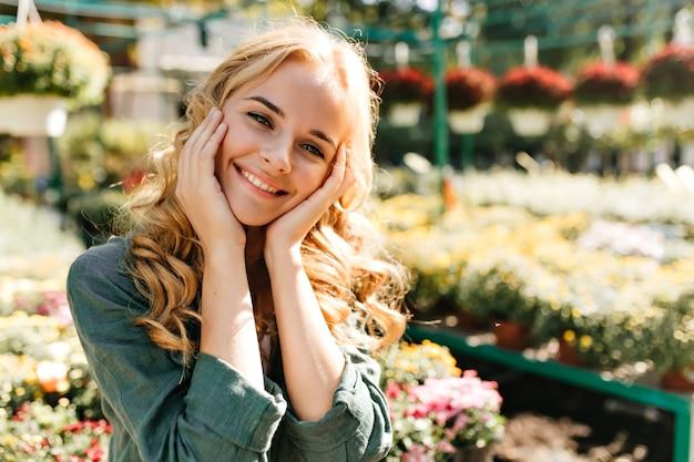 벨트가 달린 녹색 가운을 입은 아름다운 금발 머리와 부드러운 미소로 젊은 여자가 온실에서 일하고 있습니다. 무료 사진
